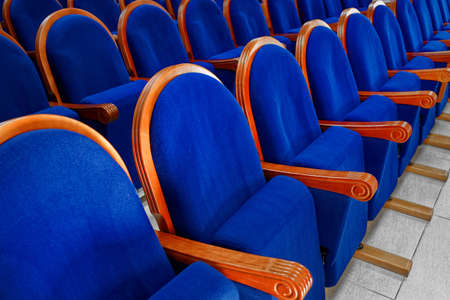 Blue velor chairs with armrests in the Assembly hall. Expensive and noble furniture in a row close-up. Place for a meeting or conference 免版税图像