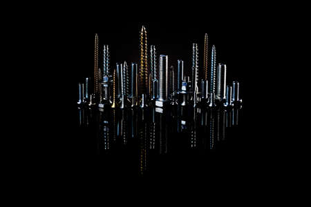 Night city of screws, bolts and nuts with reflection on a black background. The idea of advertising photos of fasteners. Installation from industrial facilities