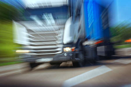 Truck in a blur on the road in motion. The danger of a collision or emergency situation. Violation of rules by truckers. The concept of vigilance at the wheel