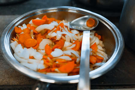 Carrots and onions are stewed in a large shiny plate on the stove. Vegetables are prepared for eating. Close up 免版税图像 - 159472776