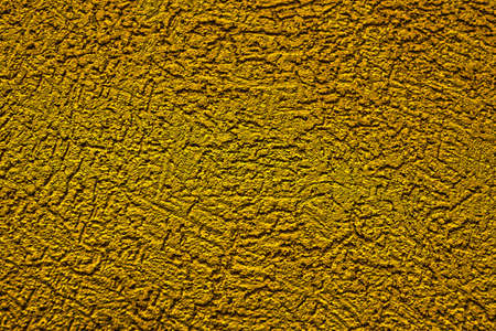 The wall is made of plaster with scratches. Rough surface. abstract background of yellow color. A template for the design of a website or ad.