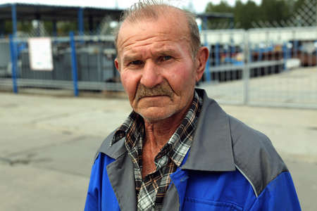 A tired and sad old man in work clothes looks at the camera. Old employee waiting for retirement