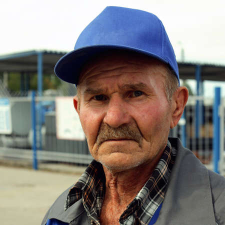 A tired and sad old man in a baseball cap with copy space looks at the camera.Portrait of an old and sad worker outdoors