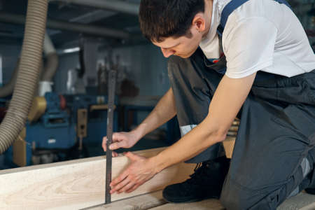 A young man works in a carpentry shop. An employee measures wood with a ruler