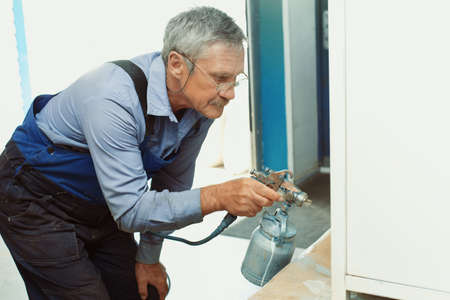 Painting of metal products. An elderly man paints a Cabinet with a compressor 免版税图像