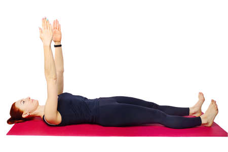 Pilates or yoga. A slim athletic girl is lying on the Mat with her arms outstretched. 免版税图像