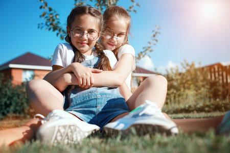 Two happy girls friends in nature. Friendly hugs of teenage girls