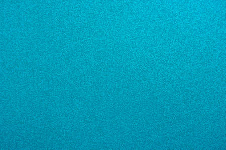 Abstract background in turquoise color. An empty, flat surface with a fine texture.