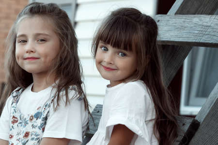 Two cute and adorable girls are sitting on a wooden staircase together. Childhood friendship. 免版税图像