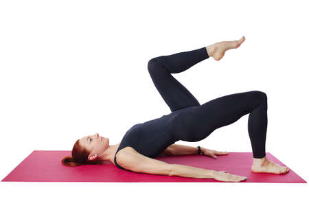 Pilates. Slender woman on the Mat performs the shoulder bridge exercise. Isolated on a white background 免版税图像