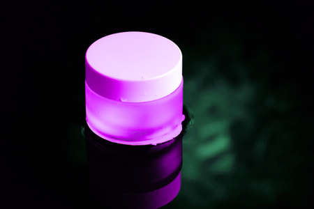 A pink glass jar with a white lid is standing in the water. The dark theme.