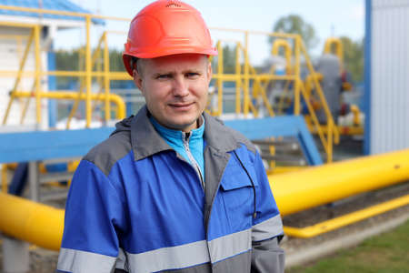 Engineer in hard hat and overalls at the production facility. a real portrait of a gas industry worker.