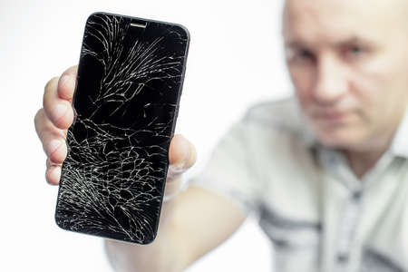 Phone With A broken screen close-up. A white man is holding a black smartphone with a cracked display.