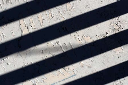 White painted surface with black stripes from the shade. 免版税图像