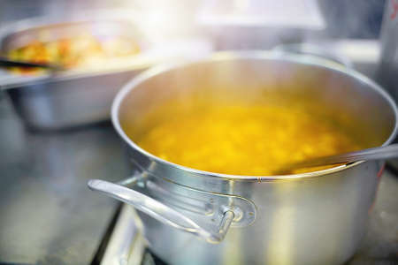 Preparation of the first course in the dining room. Soup or chowder is cooked in an aluminum pot on an electric stove.