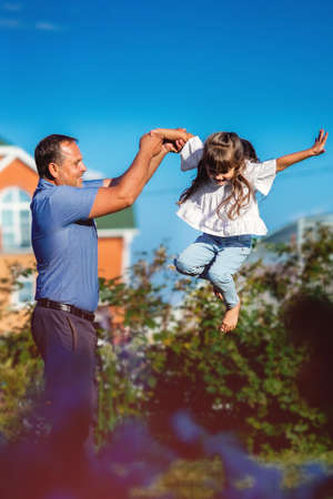 Happy girl with her father frolics on a summer day in nature. A small child jumps high with the help of his father.