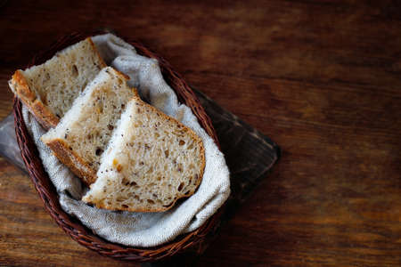 Pieces of sliced bread lie in a wicker basket on a wooden table. Fresh homemade baking of yeast-free bread with your own hands. 免版税图像