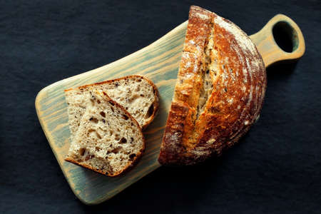 Fresh homemade bread lies on a cutting board on a dark background. Crunchy French sourdough bread. Fresh baked goods with cereals with your own hands.
