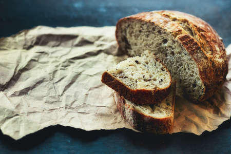 It is a loaf of fresh crusty bread with cereals on sourdough. Yeast-free homemade cakes close-up.