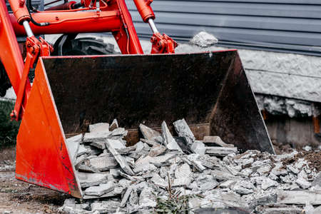 Removal of construction debris. The bucket of the tractor is filled with concrete debris and paving slabs.