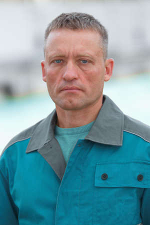 Portrait of a worker in uniform. A serious and focused Caucasian man in blue overalls with space for a layout