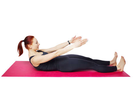 Pilates or yoga. A slender athletic girl performs an exercise on the mat to bend the spine, neck and chest.