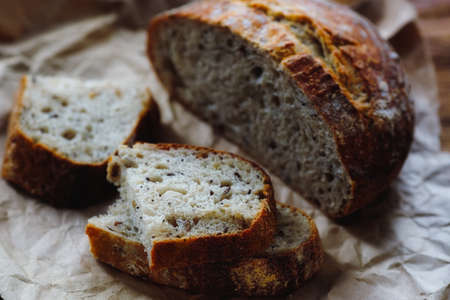 Homemade bread with cereals lies on rough craft paper. Delicious and fresh pastry made with your own hands.