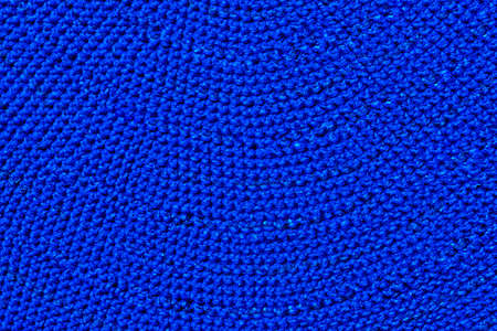 Large wool knitting of blue color. Solid surface