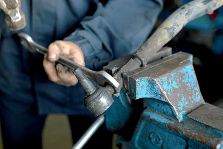 An employee of an auto repair shop has clamped the steering rod in a vise and is repairing it. Close-up 免版税图像