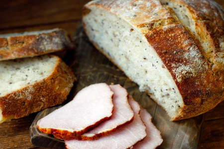 Healthy breakfast. Fresh crunchy homemade bread and ham lie on the cutting board. Homemade cakes with cereals. 免版税图像