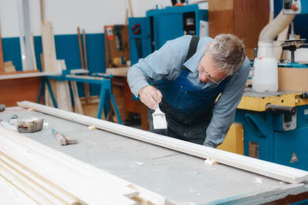 An elderly cabinetmaker in overalls and glasses paints a wooden board with a brush on a workbench in a carpentry shop.