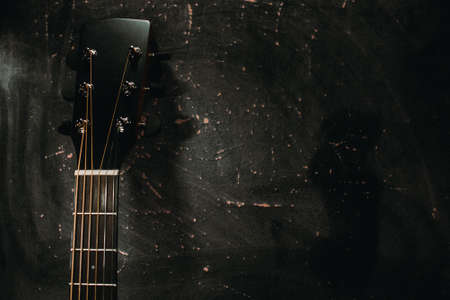 An acoustic guitar stands against the wall against a dark background.