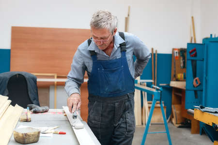 An elderly cabinetmaker in overalls and glasses paints a wooden board with a roller on a workbench in a carpentry shop.