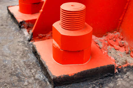The red metal support is bolted to the concrete base with large bolts. Fixing a tower or tower to the ground. 免版税图像