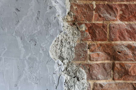 Grey concrete surface with red brick masonry. Composite abstract background with space to copy.