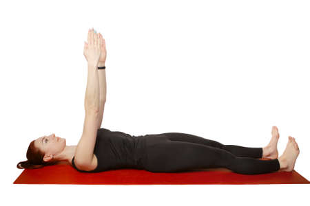 Pilates or yoga. A slender athletic girl lies on her back on a mat with her hands raised in the air.