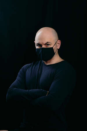 A serious bald man in a black medical mask crossed his arms over his chest. Portrait of a man on a dark background.