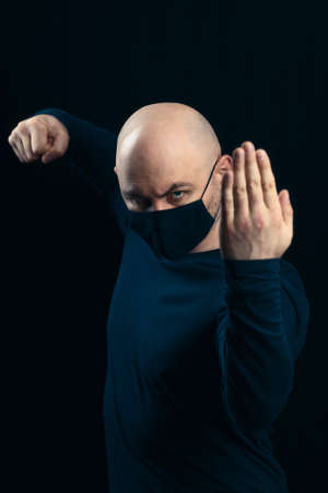 Portrait of a bald man in a black medical mask on a dark background. Threatening gestures for disease and viruses 免版税图像