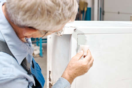 An employee paints metal products. An elderly man holds a foam sponge in his hand and paints the cabinet white.