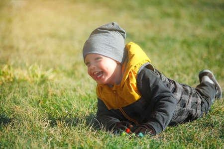 Emotional portrait of a Caucasian boy in an autumn park on a walk. 免版税图像