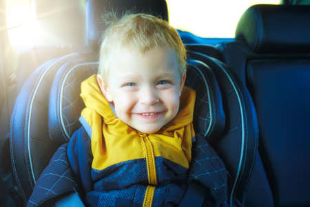 A blond toddler sits in a childs car seat and smiles. This is the happy boy in the car. Care and safety while driving.