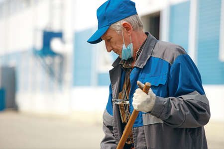 This is an elderly janitor with a broom in a medical mask on the street sweeping the territory.