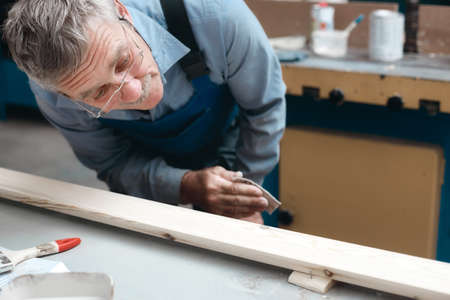 Carpenters work in the carpentry shop. An elderly male cabinetmaker carefully examines a wooden board. 免版税图像