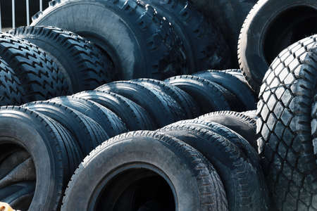 Recycling of car tires for trucks. Thats a lot of black bald rubber tires lying outside in an open warehouse.