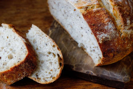 A loaf of fresh homemade bread and sliced pieces lie on a wooden table. Useful yeast-free baking with your own hands.