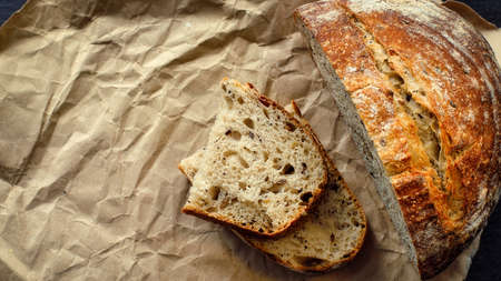 This is a loaf of fresh crusty bread with cereals on sourdough. Yeast-free homemade cakes lie on yellow craft paper. 免版税图像