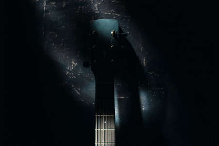 An acoustic guitar stands against the wall against a dark background. Background 免版税图像