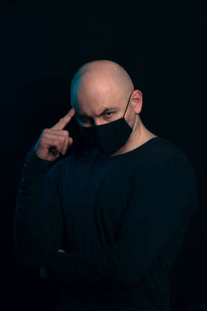 A serious bald man in a black medical mask holds a finger to his head.