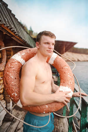 This is a young athletic guy in shorts and bare-chested standing with an old lifebuoy.