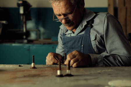 An old master with glasses works in a workshop